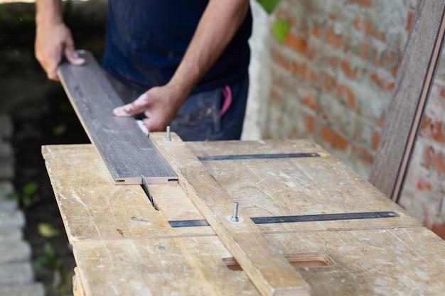 家具製造。大工が旋盤で木の板を切る。