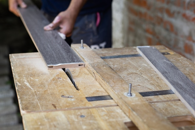 家具製造。大工が旋盤で木の板を切る。 Premium写真