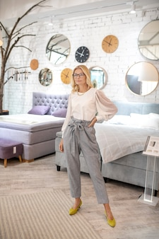 Furniture salon, beds. woman in gray trousers and yellow shoes standing near new beds in a furniture store, hand on the belt, calm.