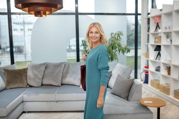 家具サロン、インテリア。家具店の大きな灰色のソファーの近くに立って、気分が良い肩にバッグを持つ女性。