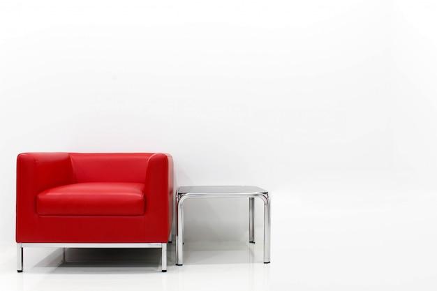 Комплект мебели красного дивана расположен рядом с белой цементной стеной.