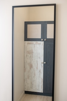 家具、ワードローブ。黒と白のドアとマットな表面、壁に立って、鏡に映るデザイナーのワードローブ