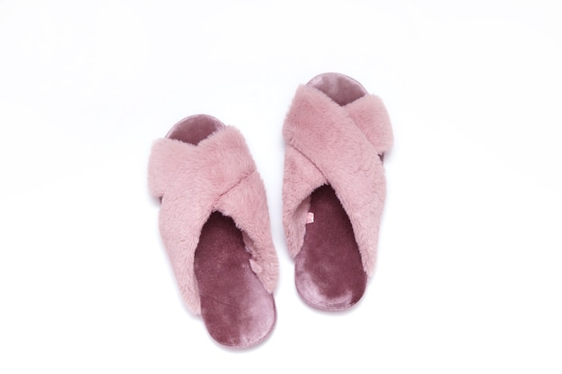 Furry pink women's slippers top view. isolated on white.