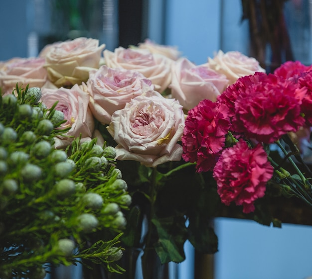 Fuscia carnations, pink roses and green blooms in one shot