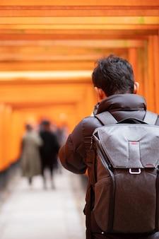 Молодой человек путешествуя на святыне fushimi inari taisha, счастливый азиатский путешественник смотря яркие оранжевые ворота torii. достопримечательности и популярные для туристов достопримечательности в киото, япония. концепция путешествия по азии