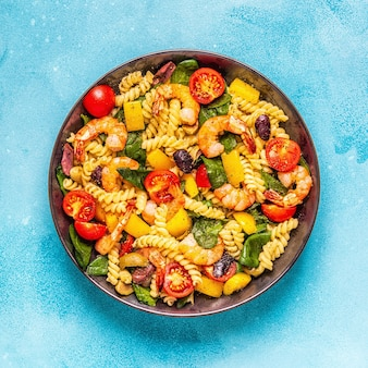 Fusili pasta salad with shrimps, tomatoes, peppers, spinach, olives