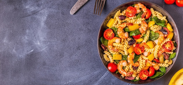 Fusili pasta salad with shrimps tomatoes peppers spinach olives