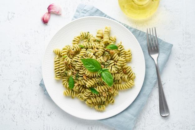 Fusili pasta with basil pesto and herbs, italian cuisine, gray stone , top view