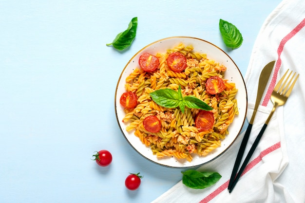 Fusilli - classic italian pasta from durum wheat with chicken meat, tomatoes cherry, basil in tomato