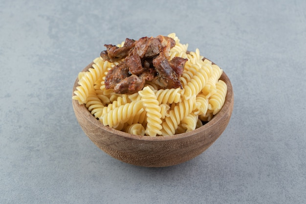 Fusilli and fried chicken in wooden bowl.