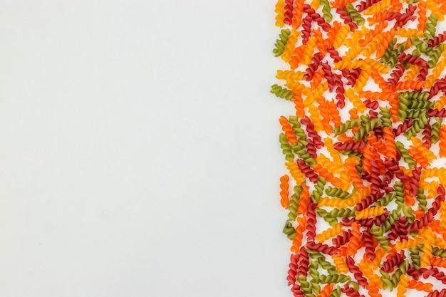 흰색 배경, 수평 방향, 복사 공간, 위쪽 보기에 있는 fusilli 여러 가지 빛깔의 파스타