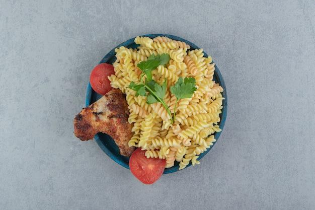 Паста фузилли и куриное крыло на синей тарелке.