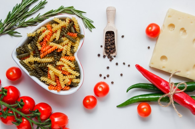 Fusilli pasta in a bowl with peppers, tomatoes, cheese, plant, peppercorns flat lay on a white table