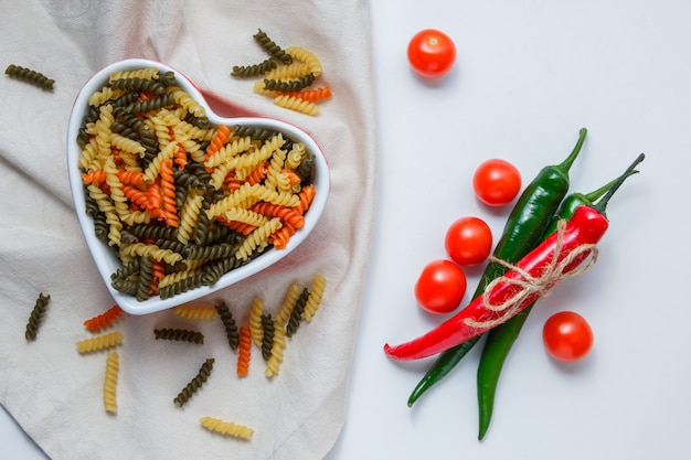 Fusilli pasta in a bowl with peppers, tomatoes flat lay on white and tablecloth table