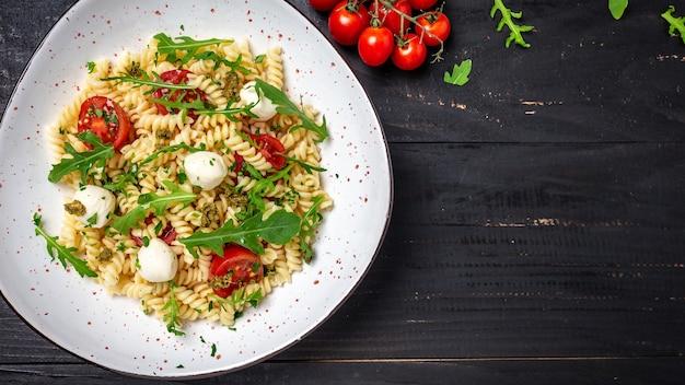 フジッリパスタカプレーゼサラダ、チェリートマトとモッツァレラチーズの黒い木製テーブル。バナー、テキストのメニューレシピの場所、上面図。