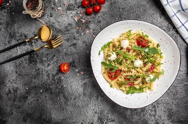 フジッリパスタカプレーゼサラダ、チェリートマトとモッツァレラチーズ。ベジタリアンサラダ、野菜ペースト。バナー、メニュー、レシピ。健康食品。