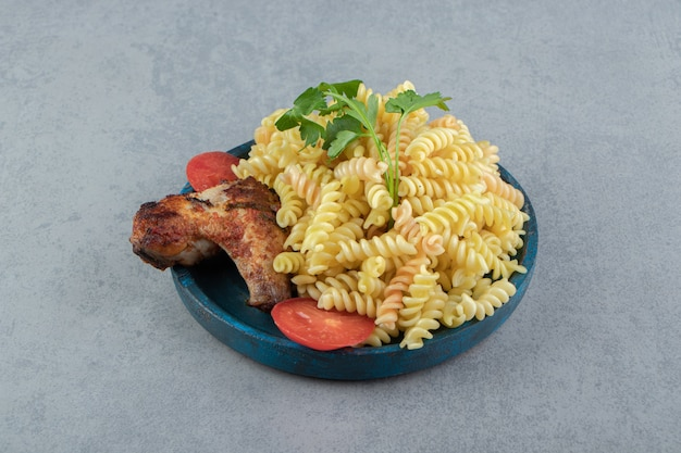 Fusilli pasta and chicken wing on blue plate