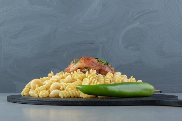 Fusilli pasta, chili pepper and chicken on black board.