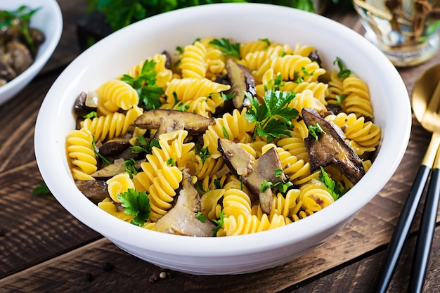 Fusilli 파스타 글루텐 무료 흰색 접시에 산림 버섯. 채식 / 비건 음식. 이탈리아 요리.