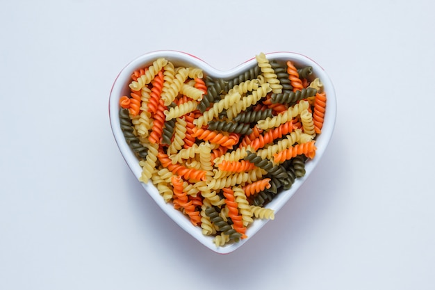 Fusilli pasta in a heart shaped bowl on white table, top view.