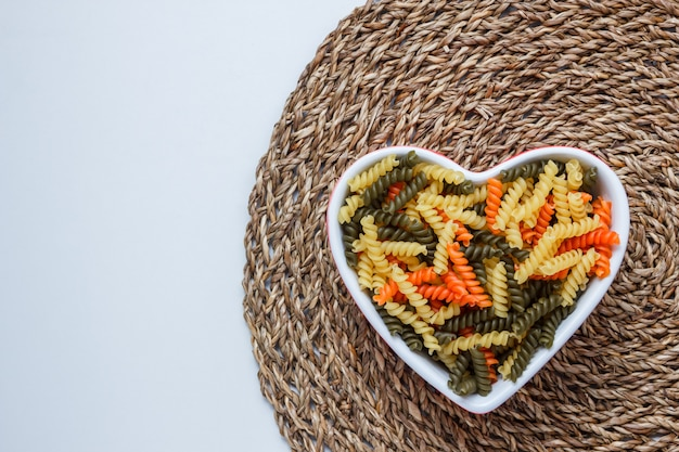 Fusilli pasta in a heart shaped bowl on white and wicker placemat table. top view.