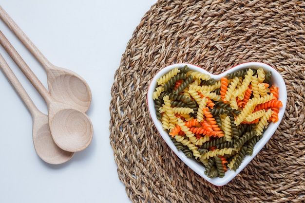 Fusilli pasta in a heart shaped bowl with wooden spoons top view on white and wicker placemat table