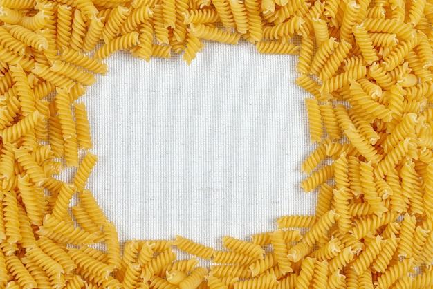 Паста фузилли в рамке на льняной ткани в деревенском стиле