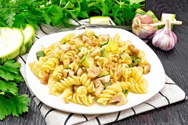 Fusilli pasta with chicken breast, zucchini, cream and pine nuts in a plate on napkin, garlic, fork and parsley on a dark wooden board background