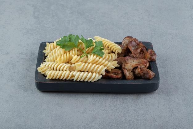 검은 접시에 닭고기와 푸실리 파스타입니다.