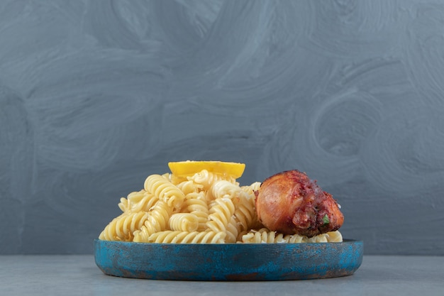 Fusilli pasta with fried chicken on blue plate.