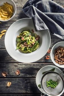 Паста фузилли с ветчиной из зеленого горошка и грецкими орехами. итальянская или средиземноморская кухня.