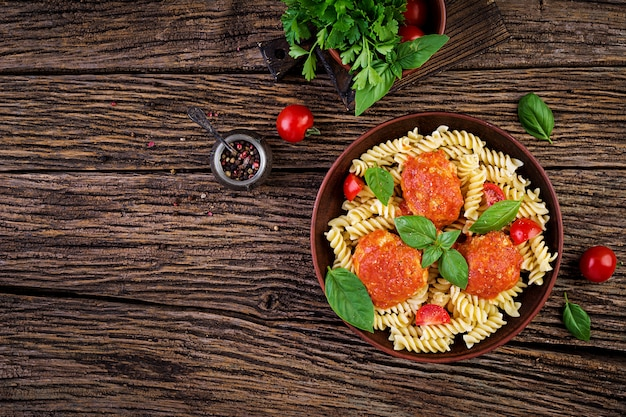 Fusilli  pasta with meatballs in tomato sauce and basil in bowl