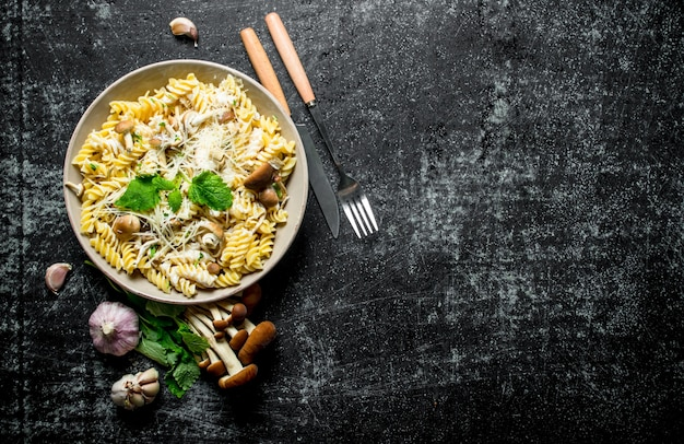 Fusilli pasta with mushrooms, garlic and mint leaves. on rustic