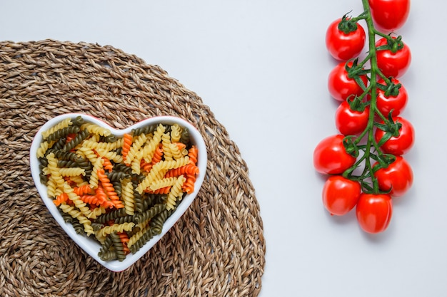 Fusilli pasta with tomato cluster in a bowl on white and wicker placemat table, flat lay.