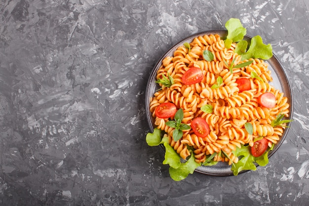 Fusilli pasta with tomato sauce cherry tomatoes lettuce and herbs on a black concrete background