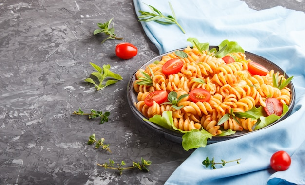 Fusilli pasta with tomato sauce, cherry tomatoes, lettuce and herbs on a black concrete
