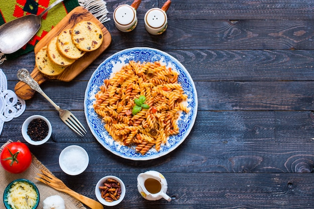 Fusilli pasta with tomato sauce tomatoes onion garlic dried paprika olives pepper and olive oil on a wooden background.