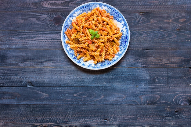 Fusilli pasta with tomato sauce, tomatoes, onion, garlic, dried paprika, olives, pepper and olive oil, on a wooden background.