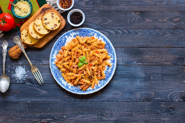 Fusilli pasta with tomato sauce, tomatoes, onion, garlic, dried paprika, olives, pepper and olive oil on a wooden table