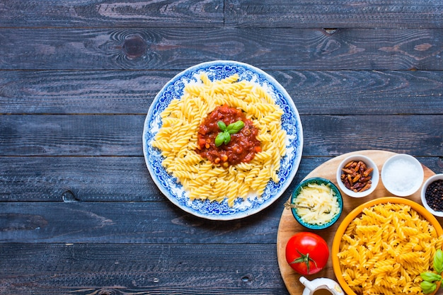 Fusilli pasta with tomato sauce, tomatoes, onion, garlic, dried paprika, olives, pepper and olive oil