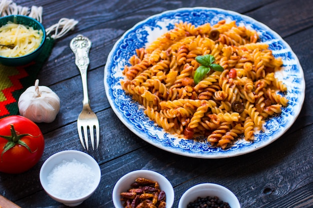 Fusilli pasta with tomato sauce, tomatoes, onion, garlic, dried paprika, olives, pepper and olive oil,.