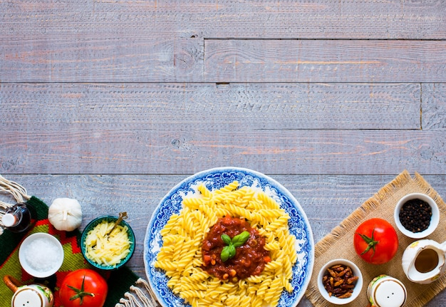 Fusilli pasta with tomato sauce and vegetables on a wooden table