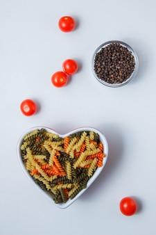 토마토, 화이트 테이블, 평면도에 그릇에 후추와 Fusilli 파스타. 무료 사진