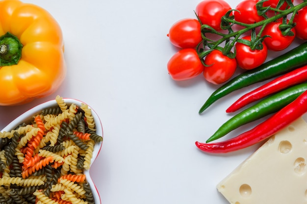 Fusilli pasta with tomatoes, peppers, cheese in a bowl on white table, high angle view.