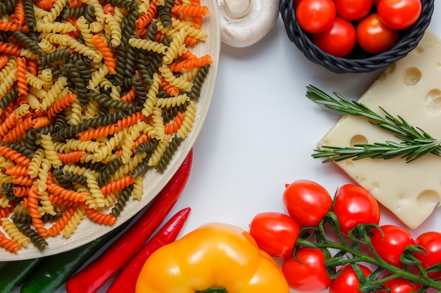 Fusilli pasta with tomatoes, peppers, mushroom, plant on cheese in a plate on white table, high angle view.