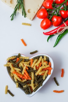 Fusilli pasta with tomatoes, peppers, plant, cheese in a bowl on white table, top view.