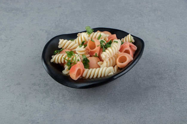 Fusilli and red seashell pasta in black bowl.
