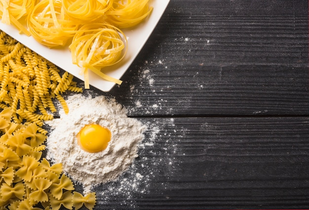 Fusilli; tagliatelle and farfalle pasta with egg yolk on flour