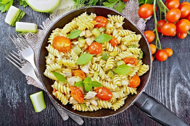 Fusilli with chicken, zucchini and tomatoes in a frying pan on burlap, forks, basil and parsley on black wooden board background from above