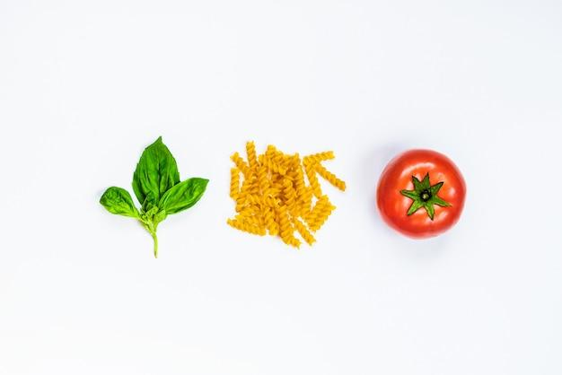 Взгляд сверху ингридиентов макаронных изделий на белой предпосылке - сырцовом fusilli, свежем базилике и зрелом томате. итальянская еда концепция.